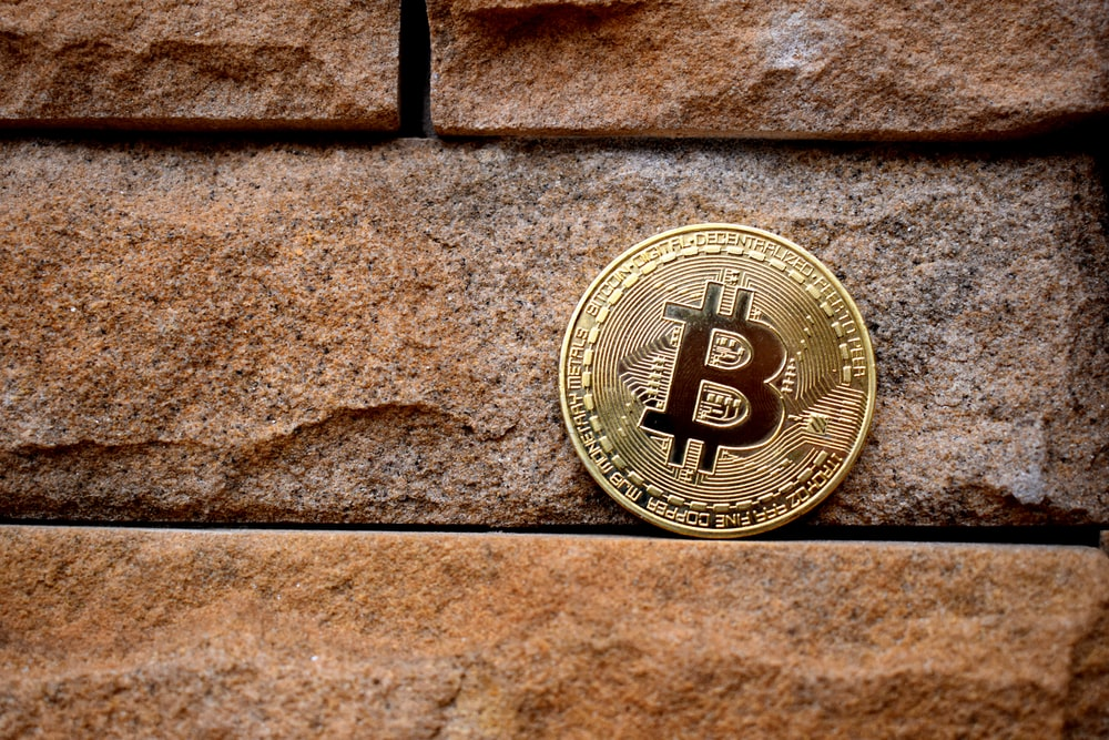 gold round coin on brown brick wall