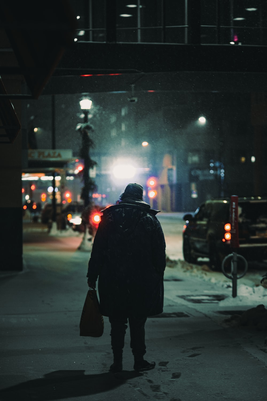 person in black coat walking on sidewalk during night time