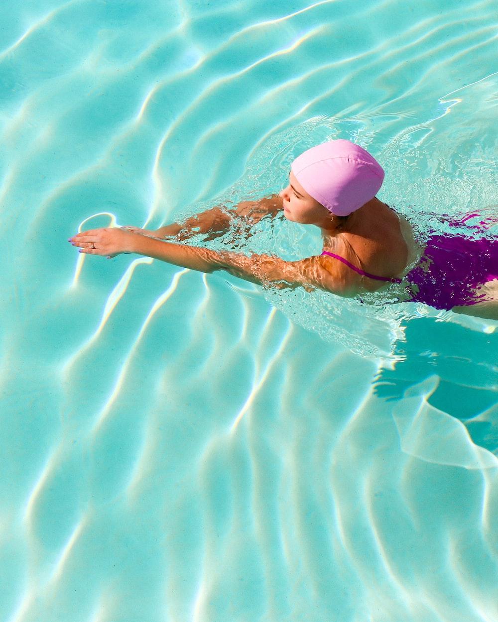 woman in pink bikini swimming on pool