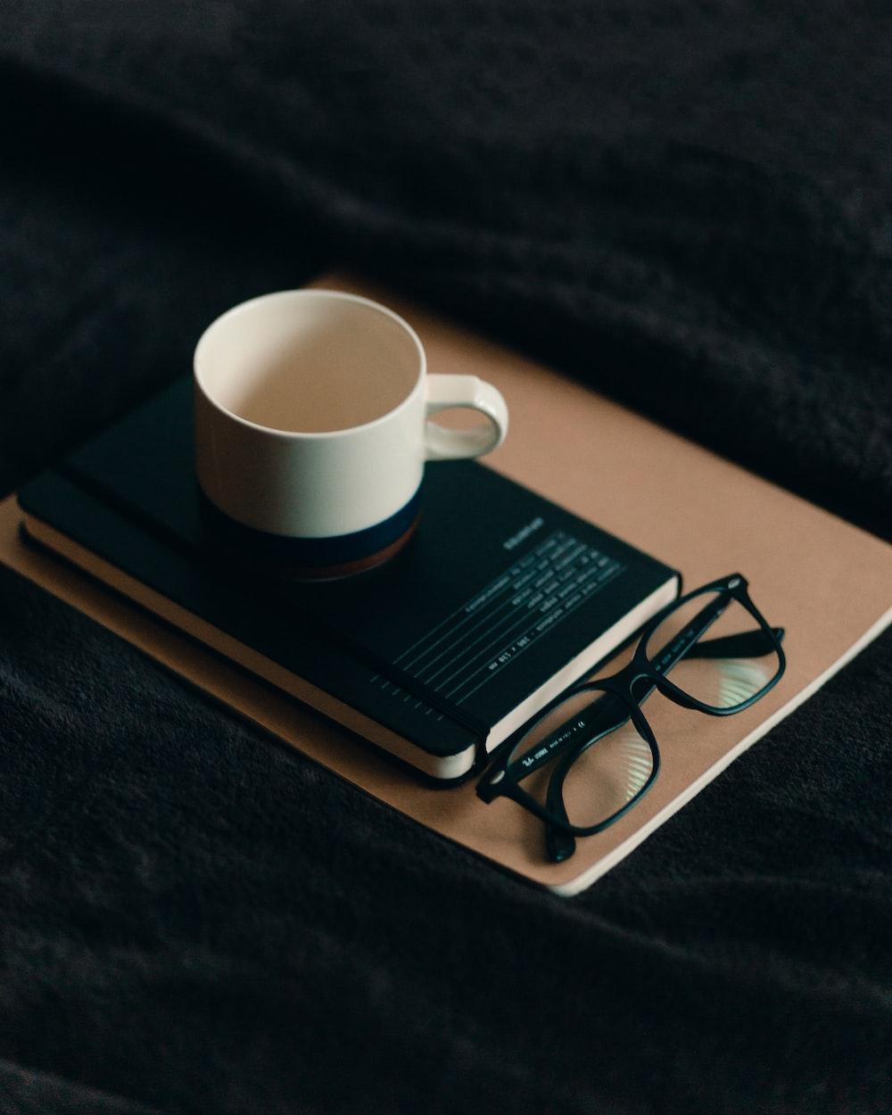 white ceramic mug on brown book