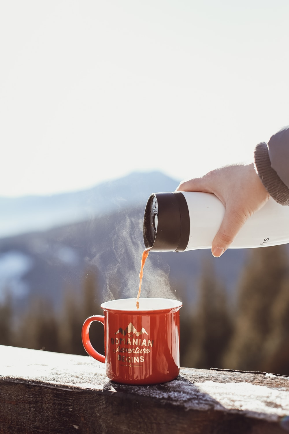 person pouring water on red ceramic mug
