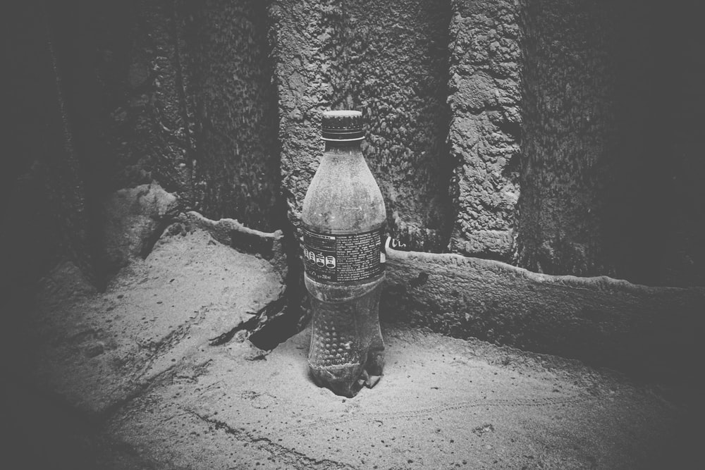 grayscale photo of plastic bottle on sand