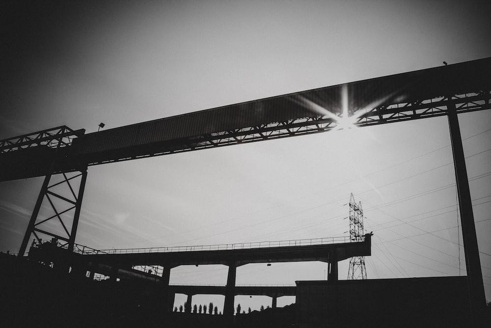 silhouette of bridge under white sky