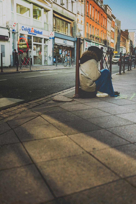 woman in white shirt sitting on sidewalk during daytime