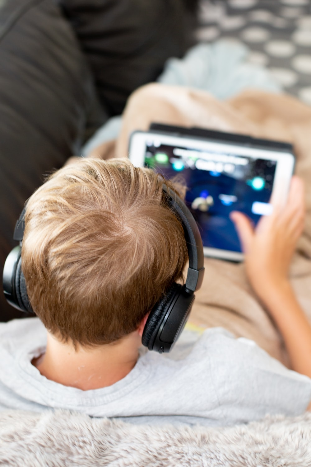 boy in white shirt using white tablet computer