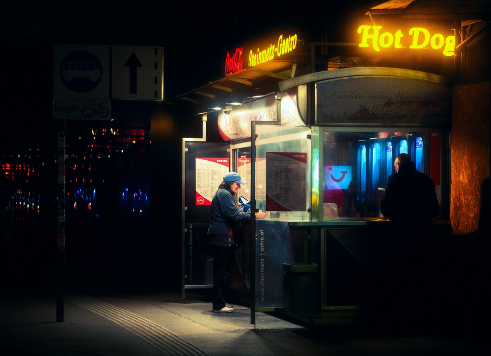 man in black jacket standing near store during night time