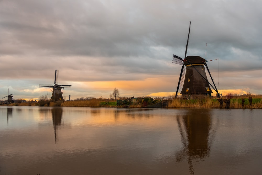windmill near body of water during sunset