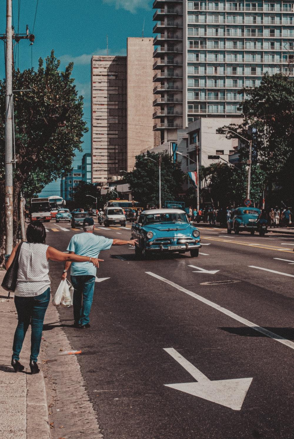 man in white dress shirt and black pants walking on pedestrian lane during daytime