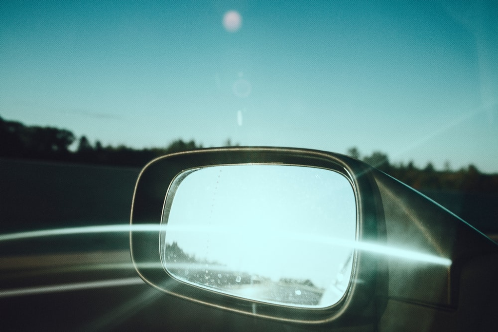 car side mirror showing green trees under blue sky during daytime