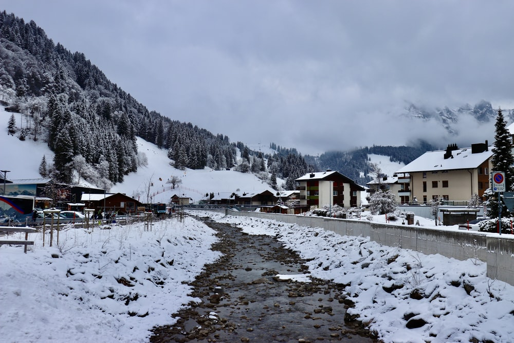 houses near snow covered mountain during daytime