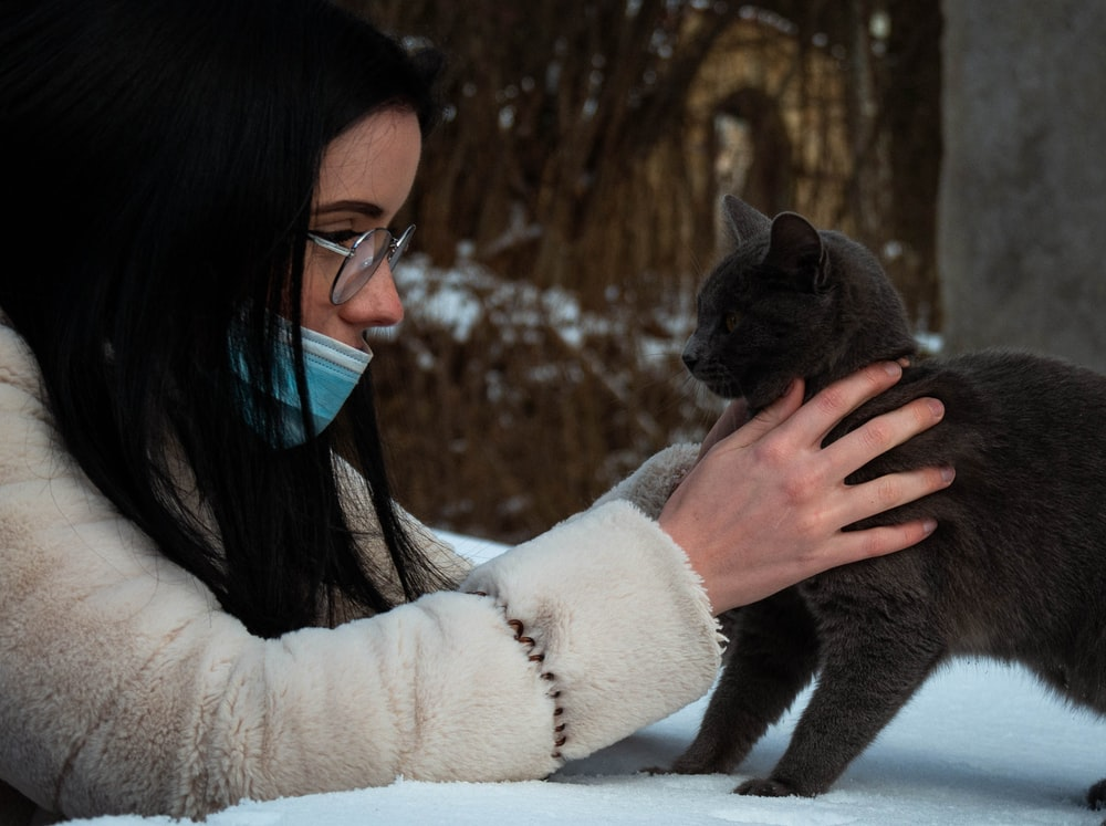 woman in white sweater holding black cat