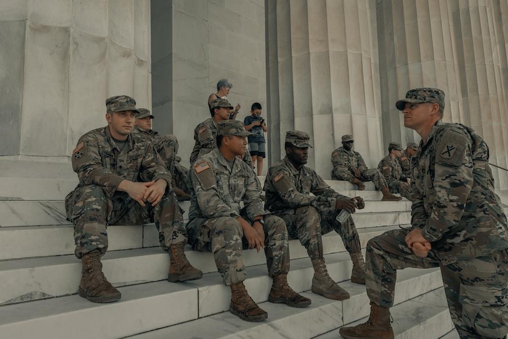 men in camouflage uniform standing near white wall