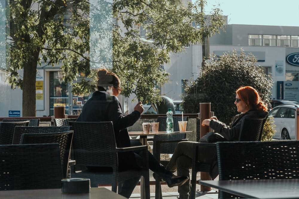 man in black suit jacket sitting on black chair