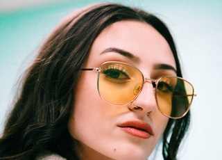 woman in white fur coat wearing gold framed aviator sunglasses
