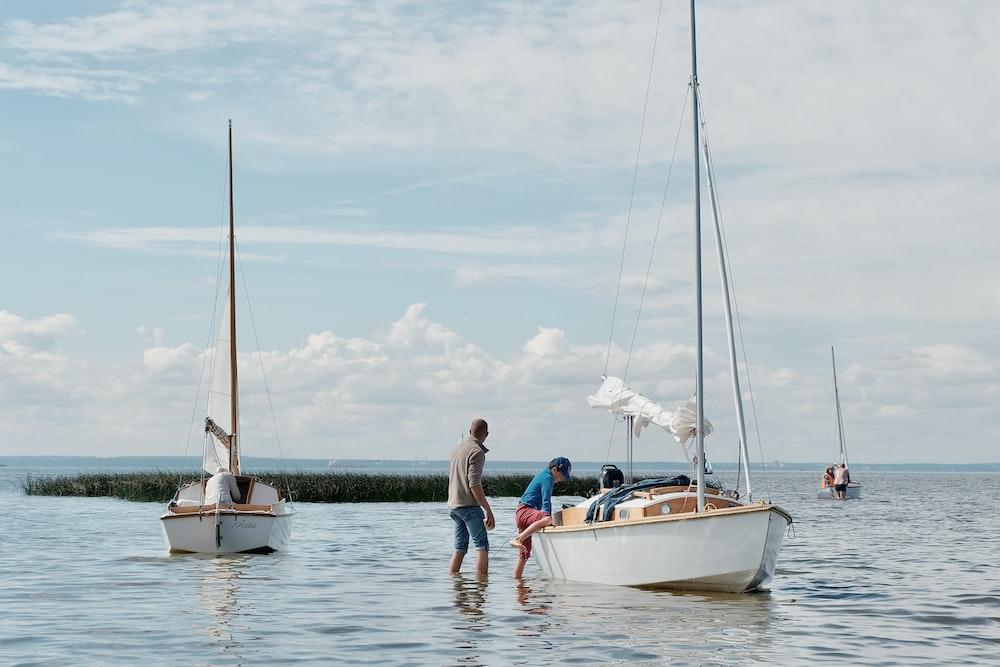 2 women sitting on white boat during daytime