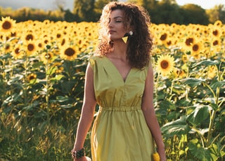 woman in yellow sleeveless dress holding white and black hair brush standing on yellow flower field