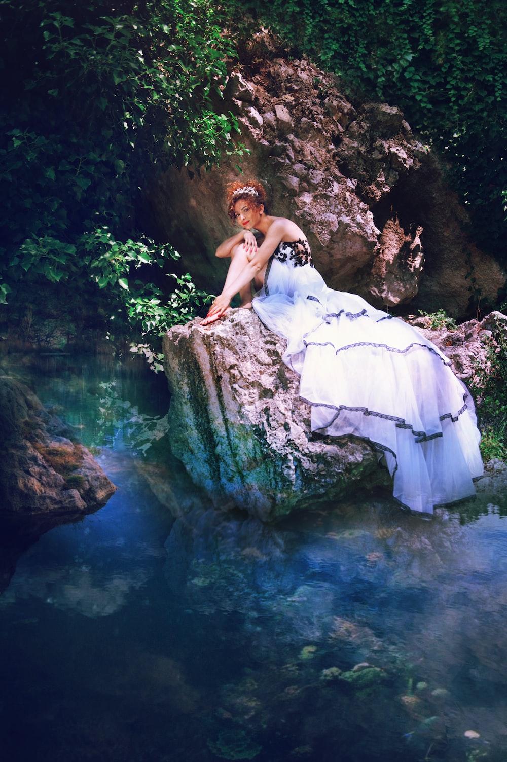 woman in white dress sitting on rock in water