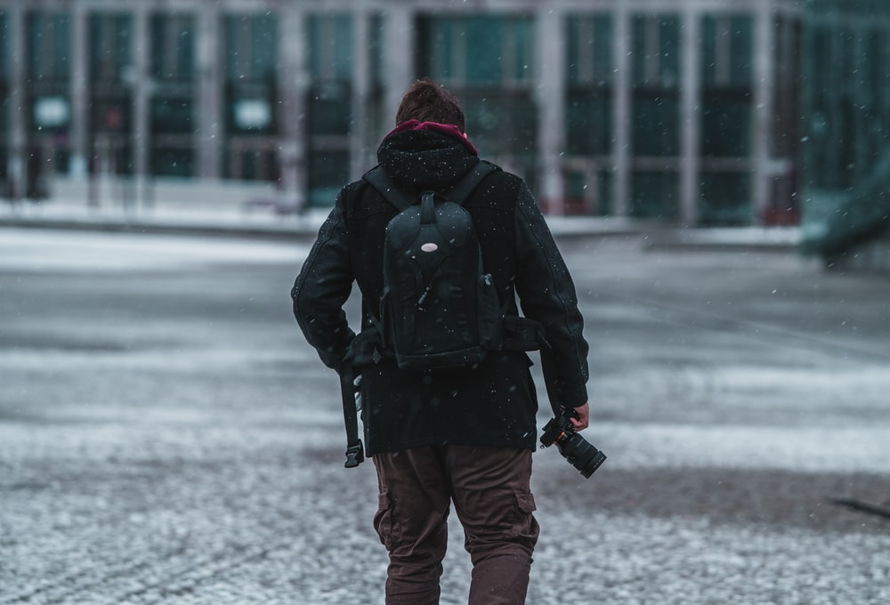 person in black jacket and red knit cap walking on snow covered ground during daytime