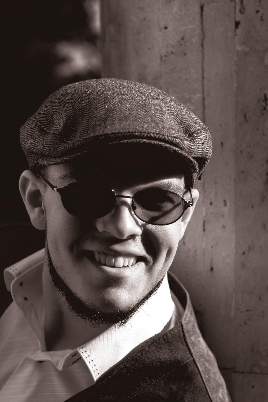 man in black framed eyeglasses and brown hat