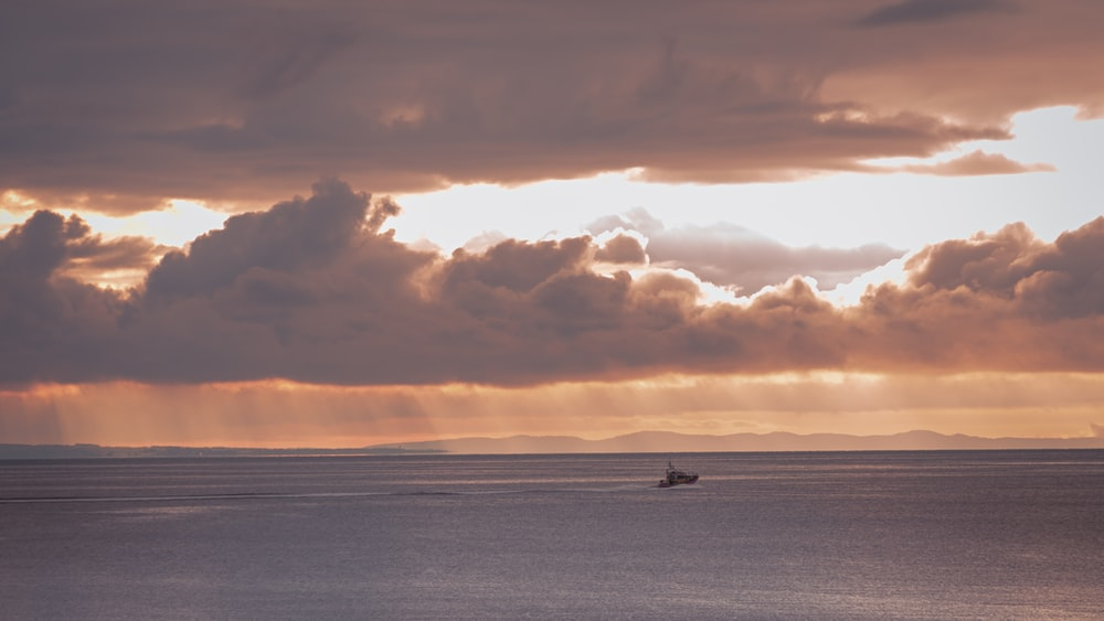 boat on sea under cloudy sky during sunset