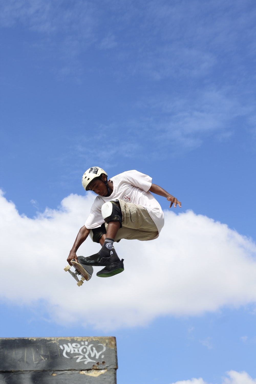 man in white t-shirt and black shorts jumping under blue sky during daytime