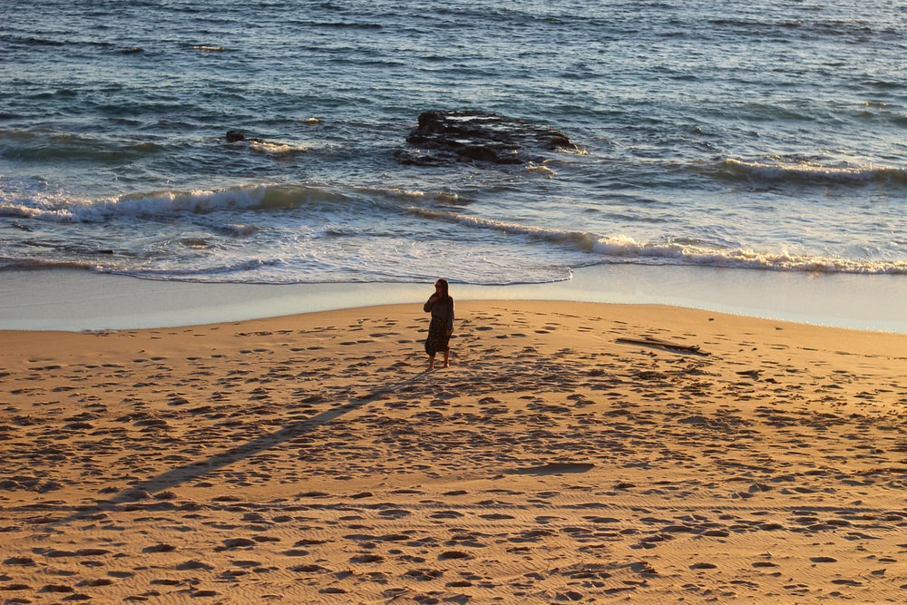 woman in black dress walking on beach during daytime