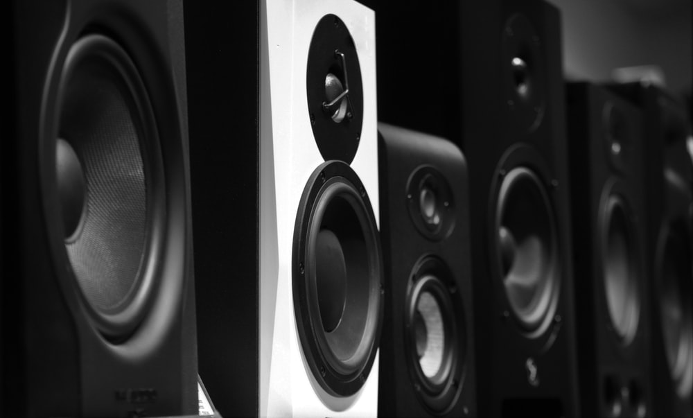 black and gray speakers on brown wooden table