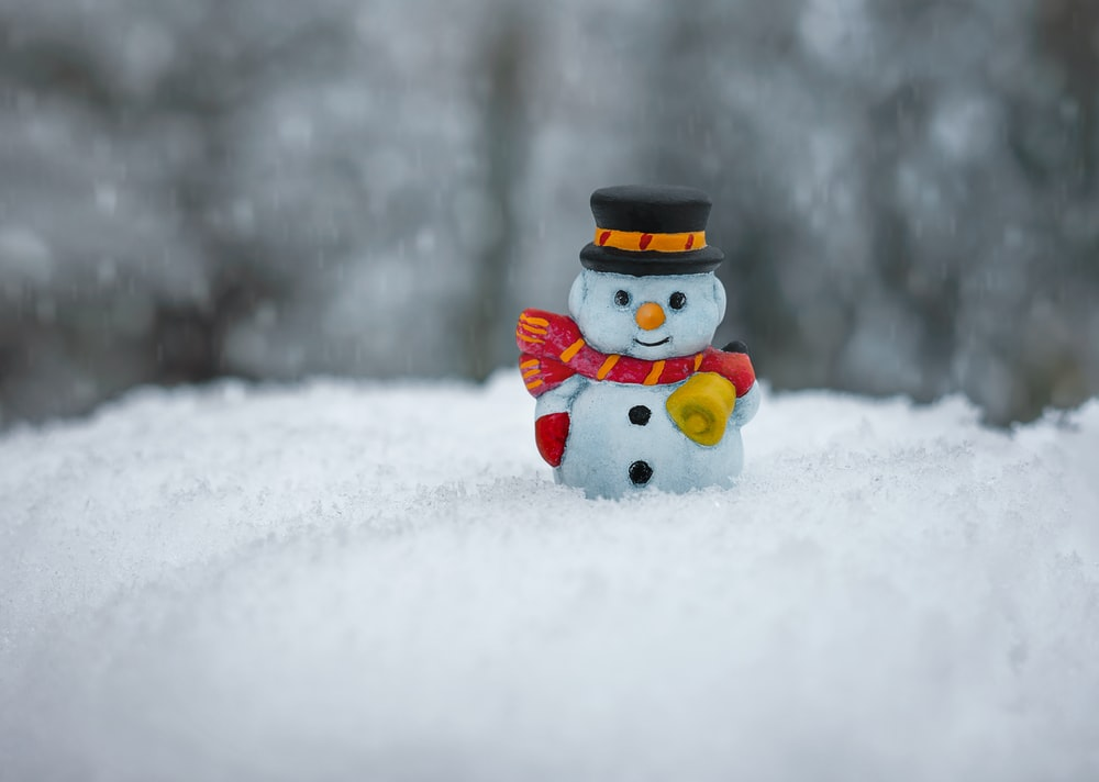 snowman in red scarf and white hat ceramic figurine