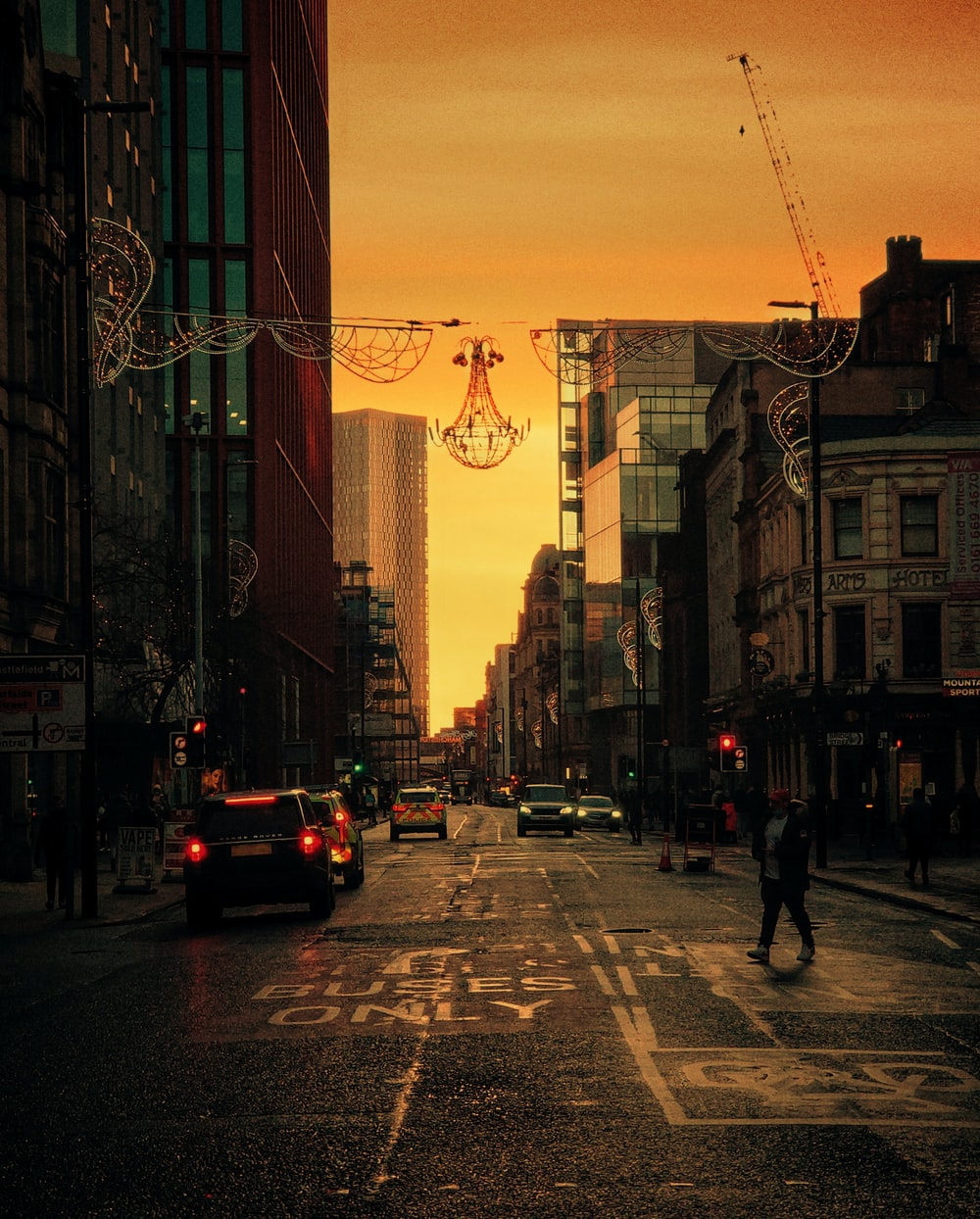 cars on road near buildings during sunset