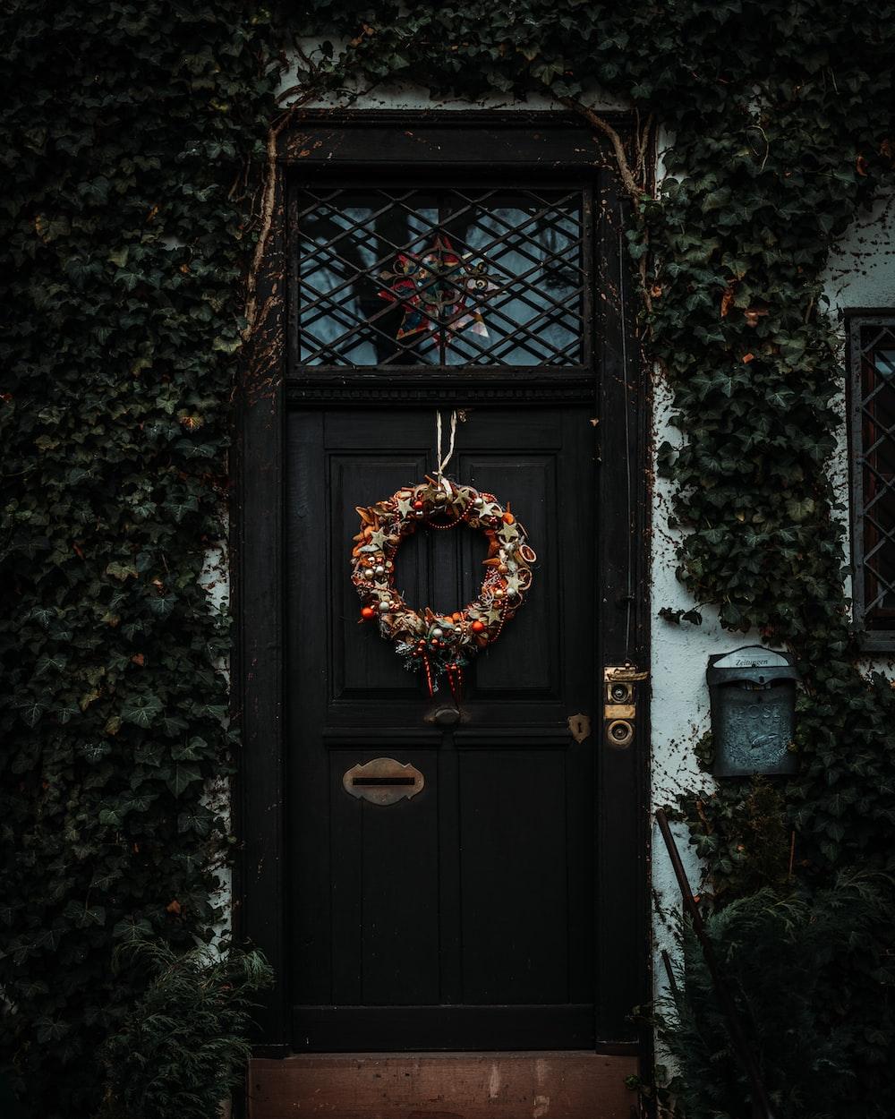 brown wreath on black wooden door