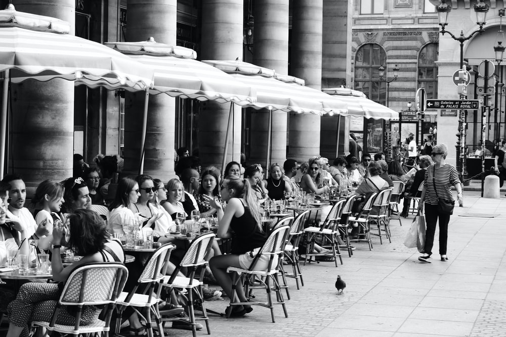 grayscale photo of people sitting on chairs