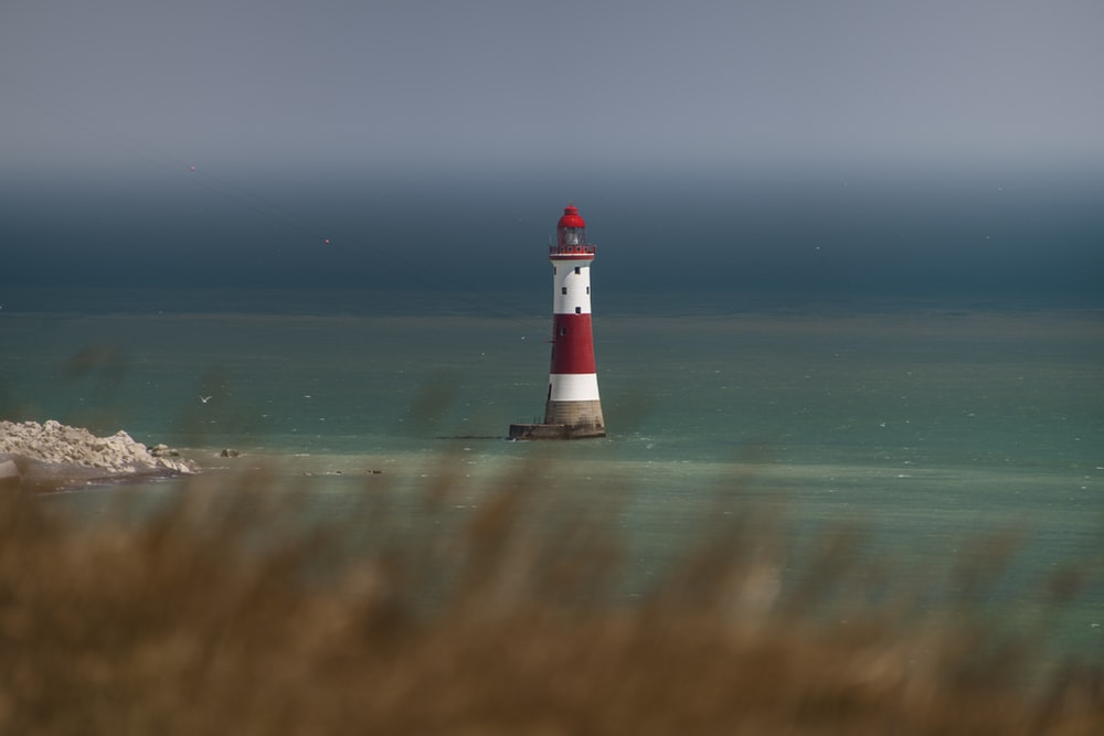 white and red lighthouse on beach during daytime