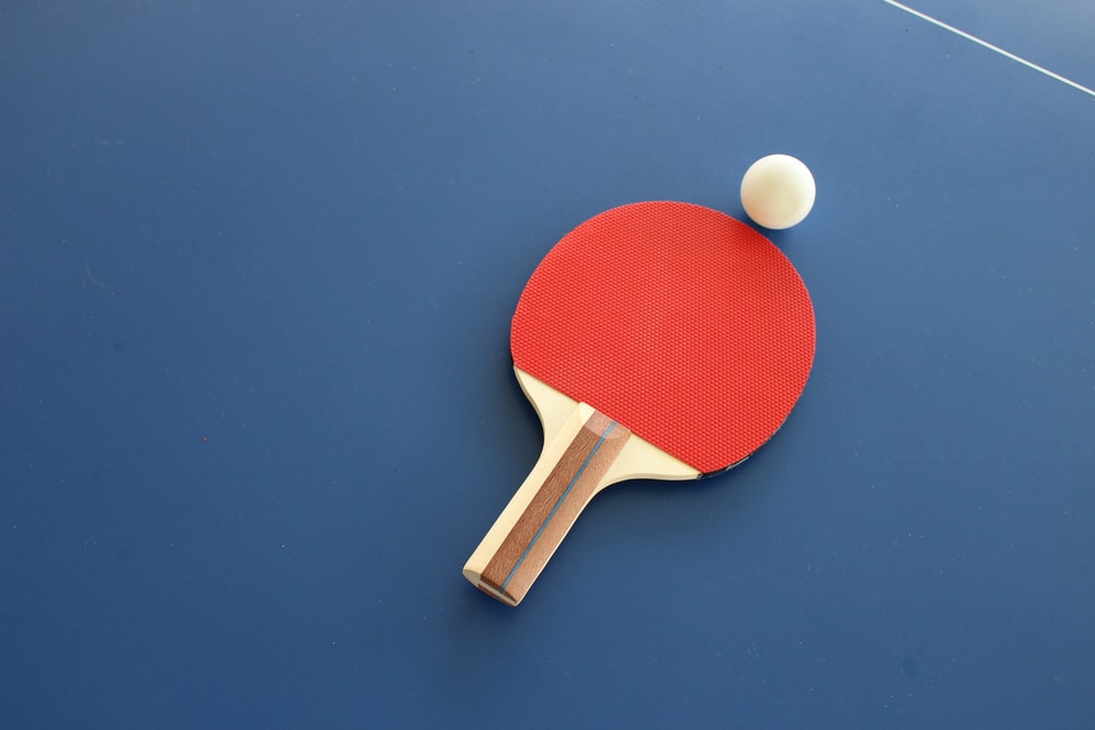 red and brown wooden table tennis racket