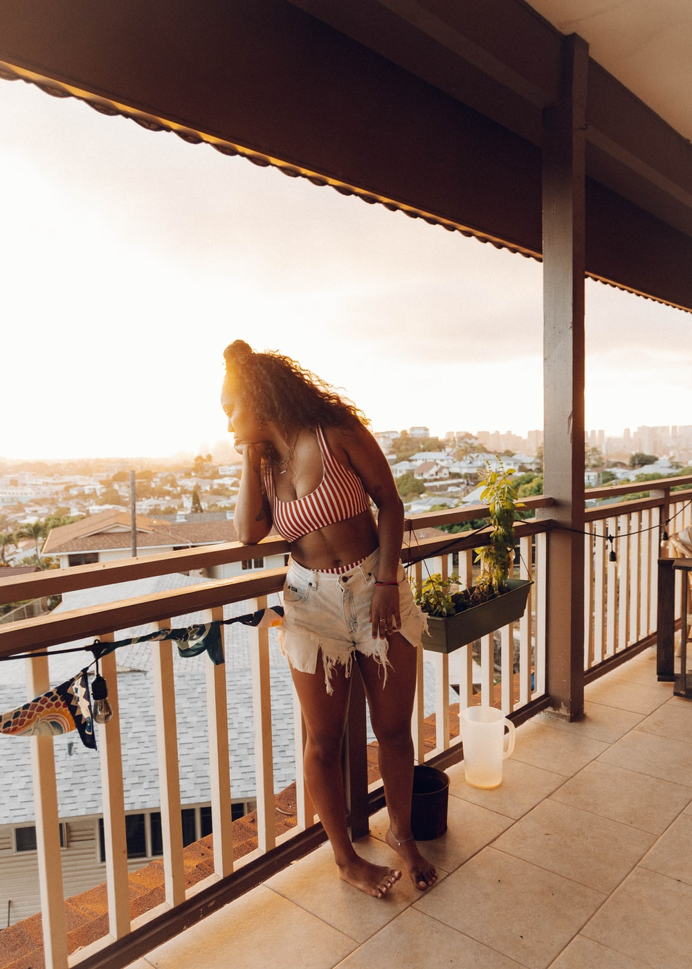 woman in white shorts standing on balcony during daytime