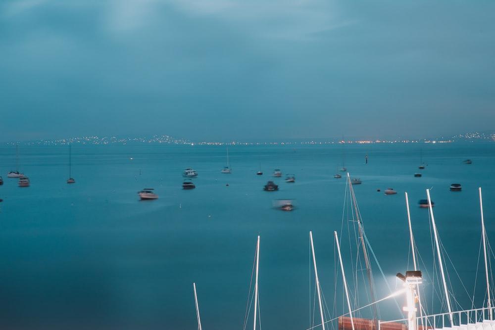 boats on sea under gray sky