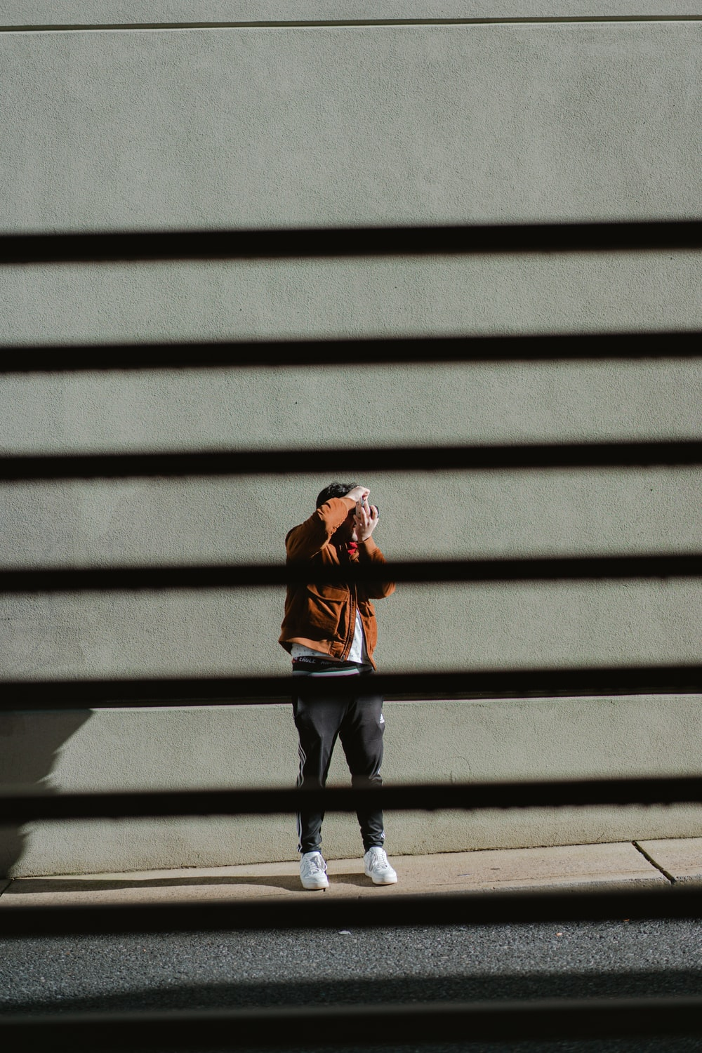 woman in brown jacket and black pants standing on gray concrete stairs