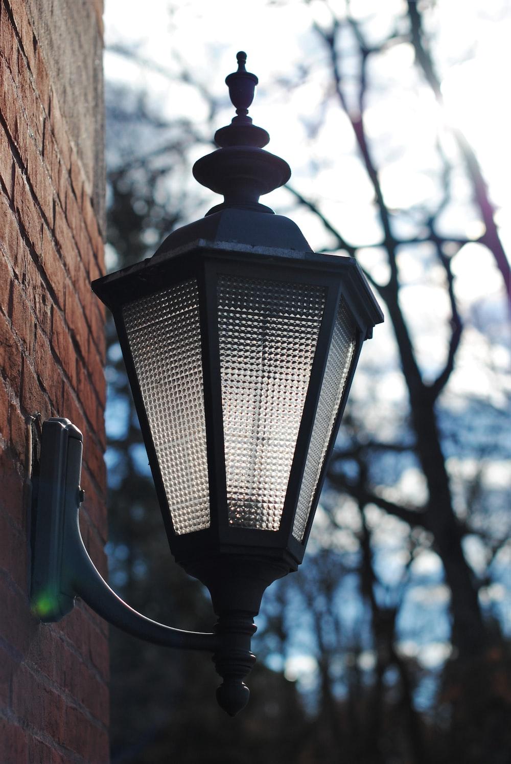 black lamp post near brown concrete wall