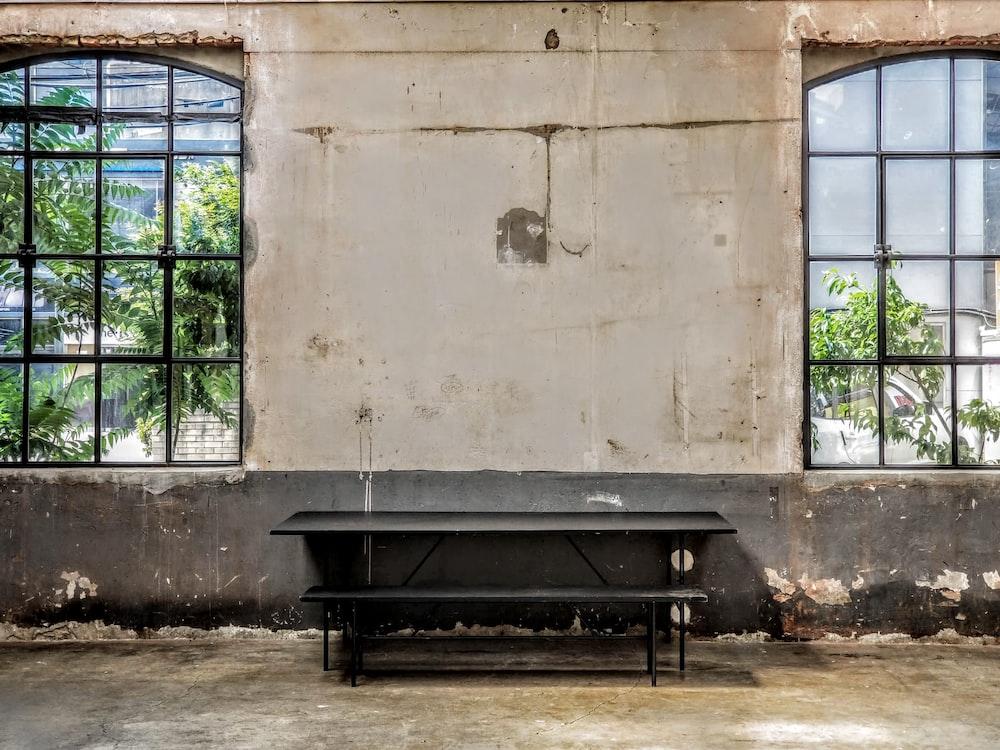 black wooden bench near brown concrete wall