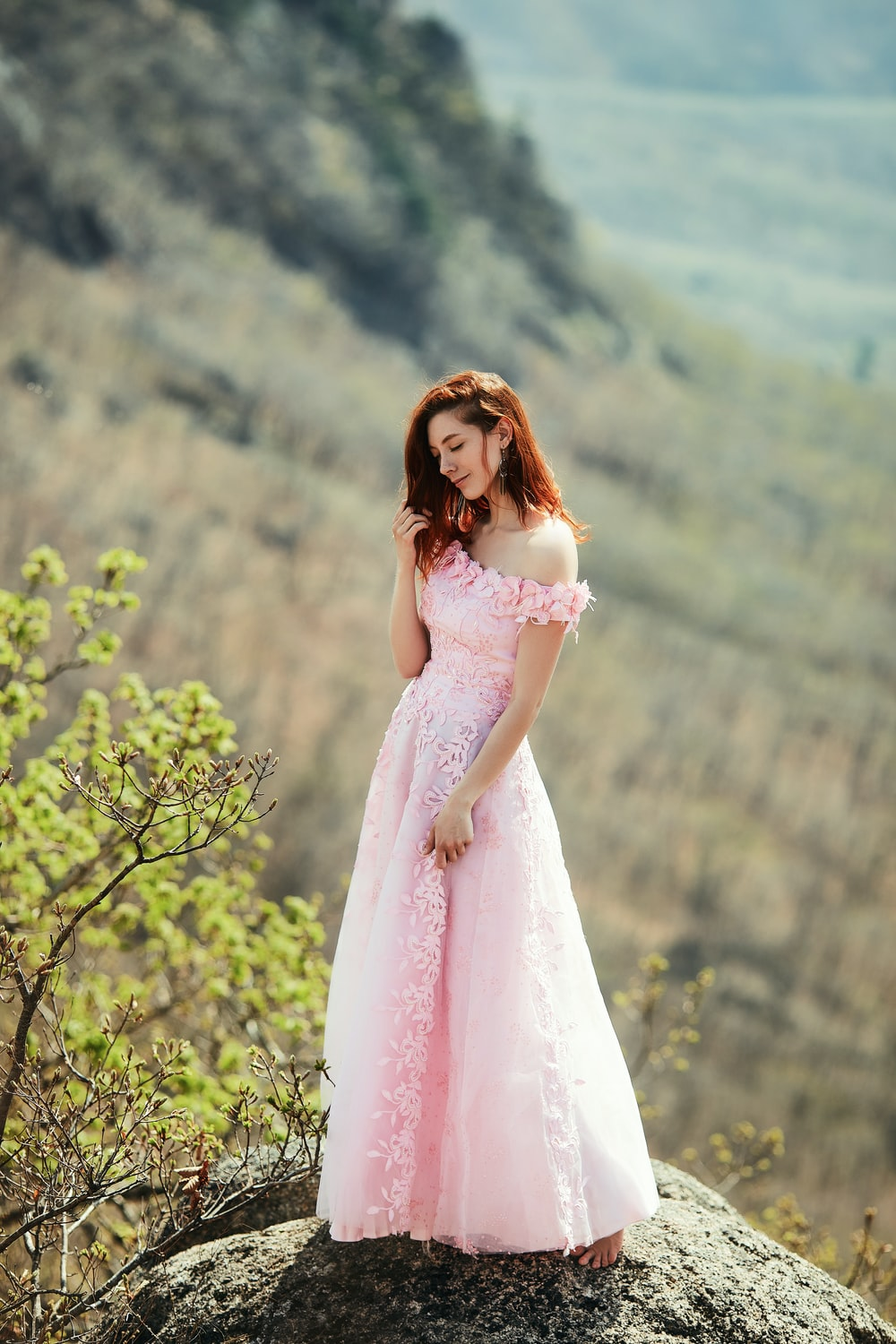 woman in pink dress standing near green tree during daytime