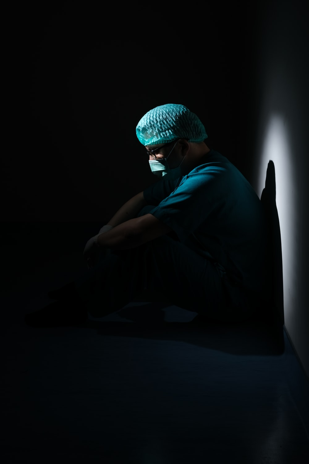 man in green shirt and blue knit cap sitting on floor