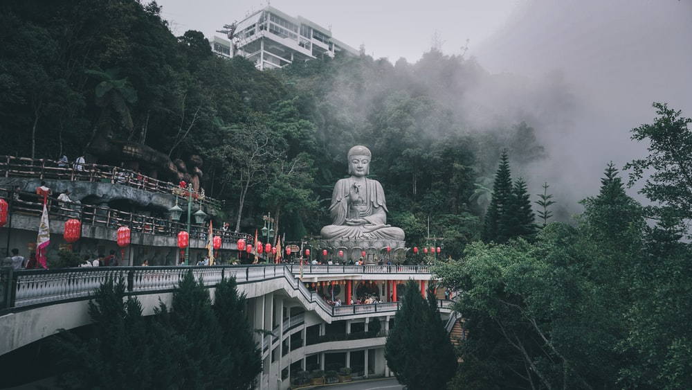 gray statue of man on top of white boat surrounded by green trees during daytime
