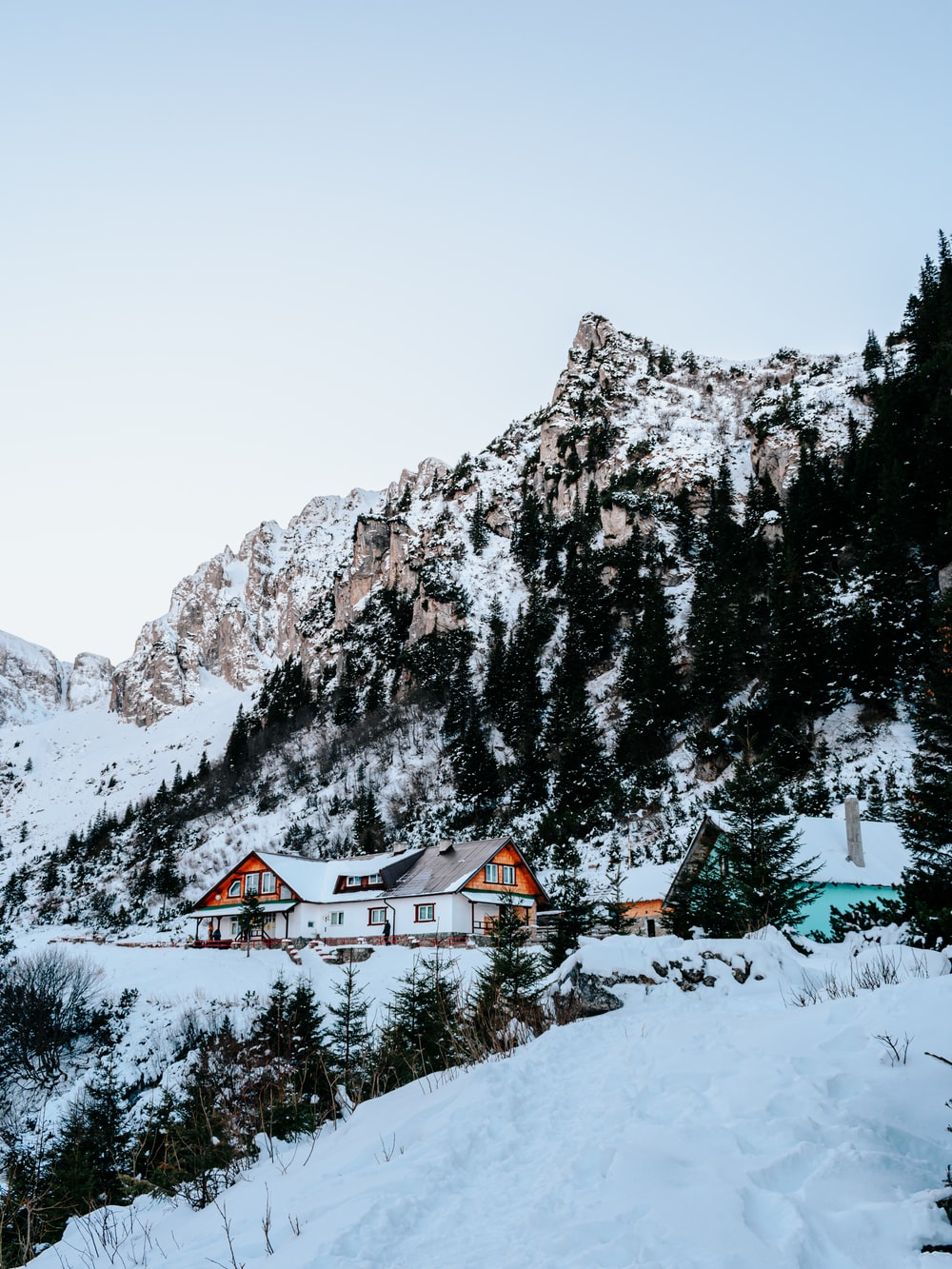 snow covered house near trees and mountain during daytime