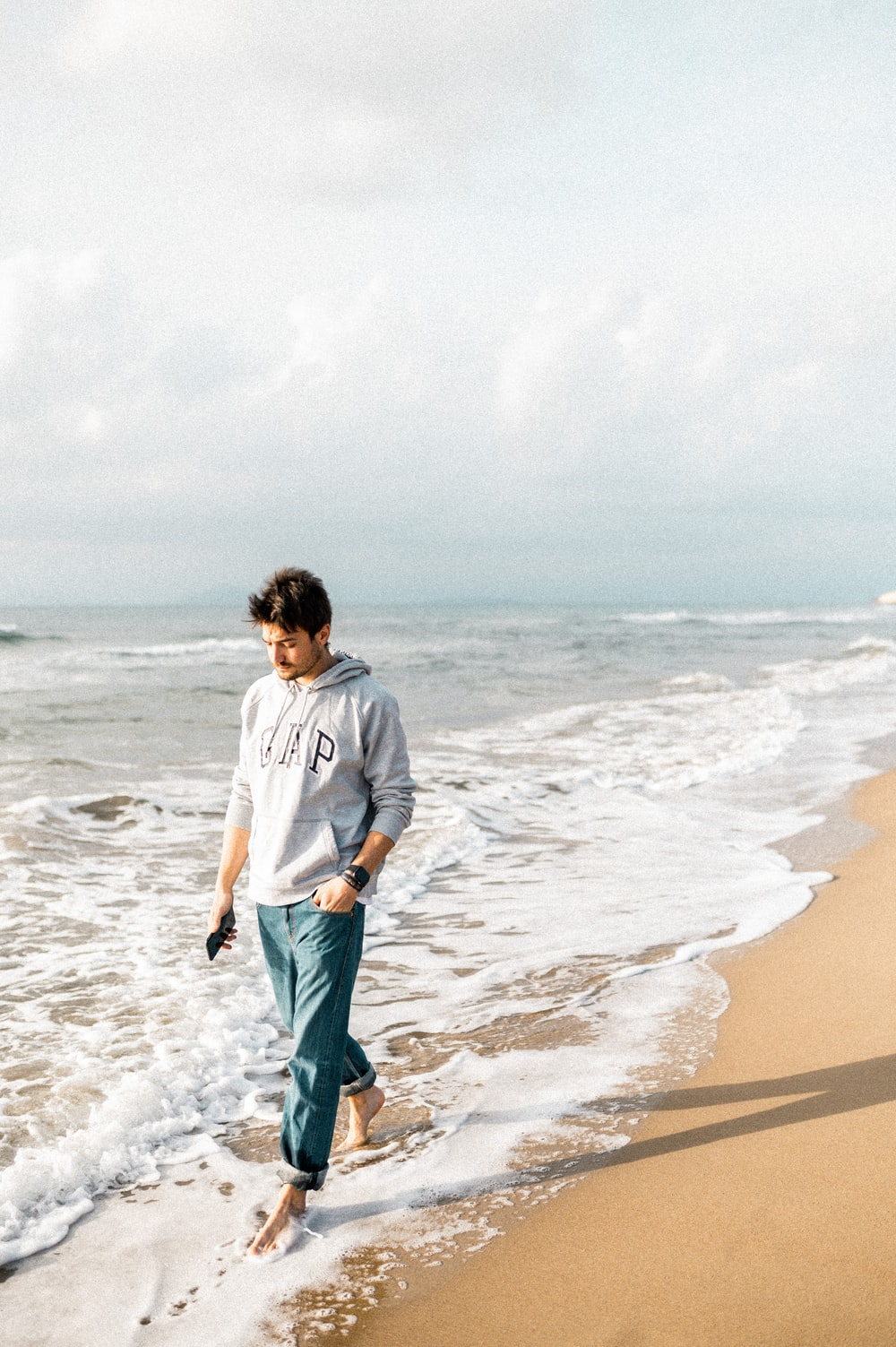 man in gray long sleeve shirt and green shorts standing on beach during daytime