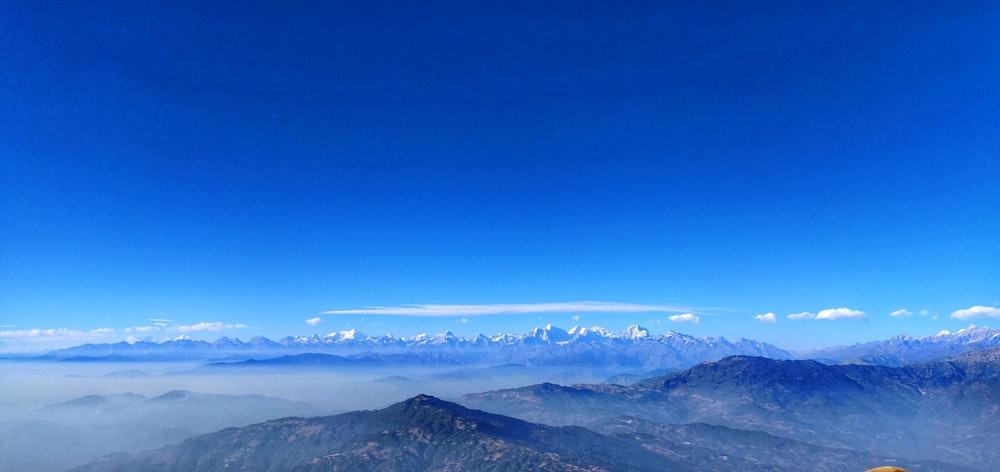 aerial view of mountains under blue sky during daytime