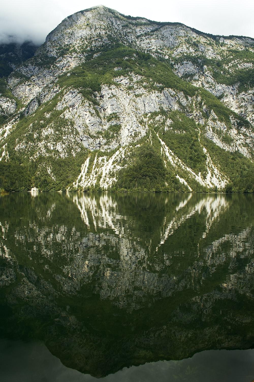 green and white mountain beside lake during daytime