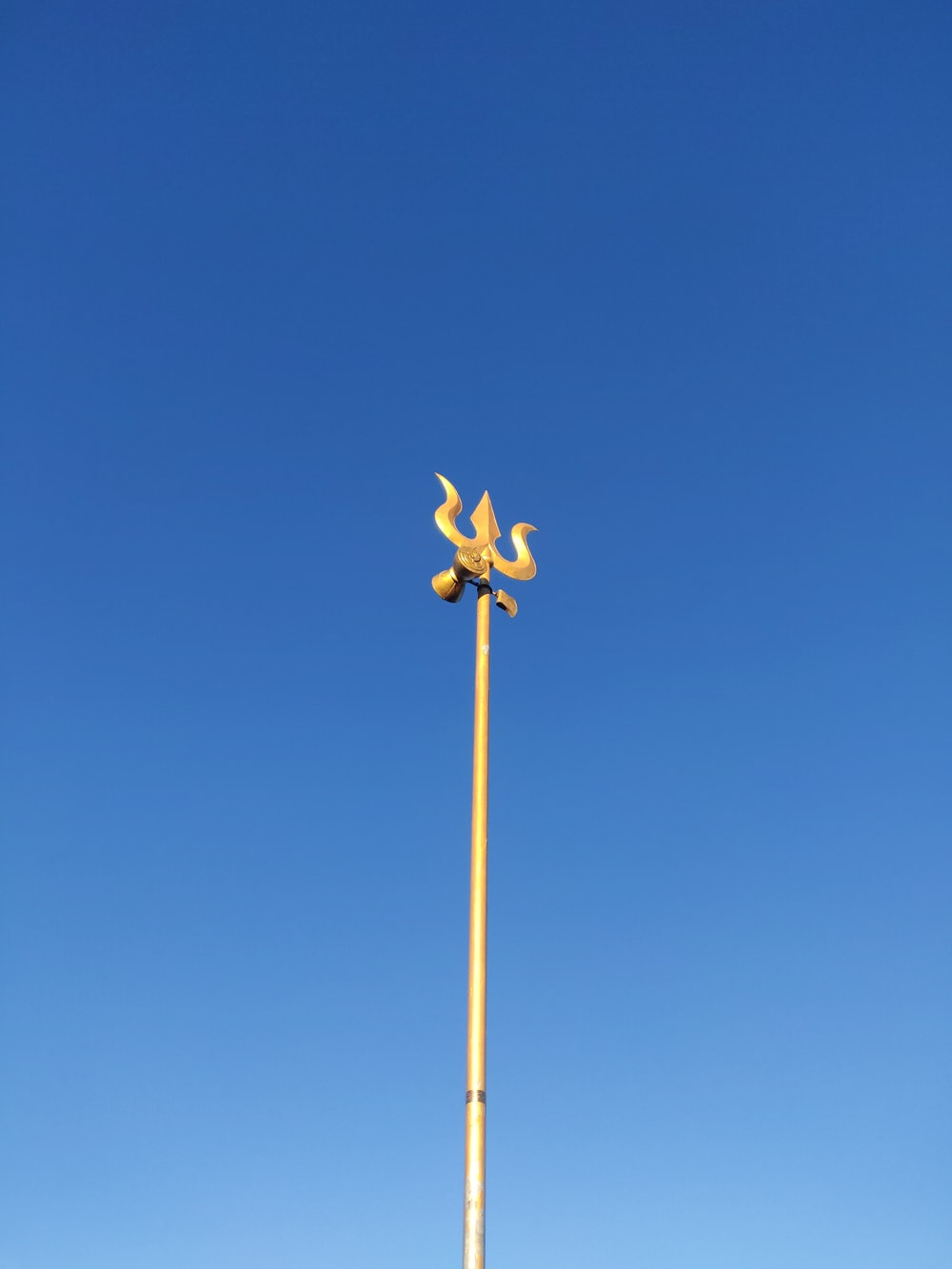 yellow and black wind mill under blue sky during daytime