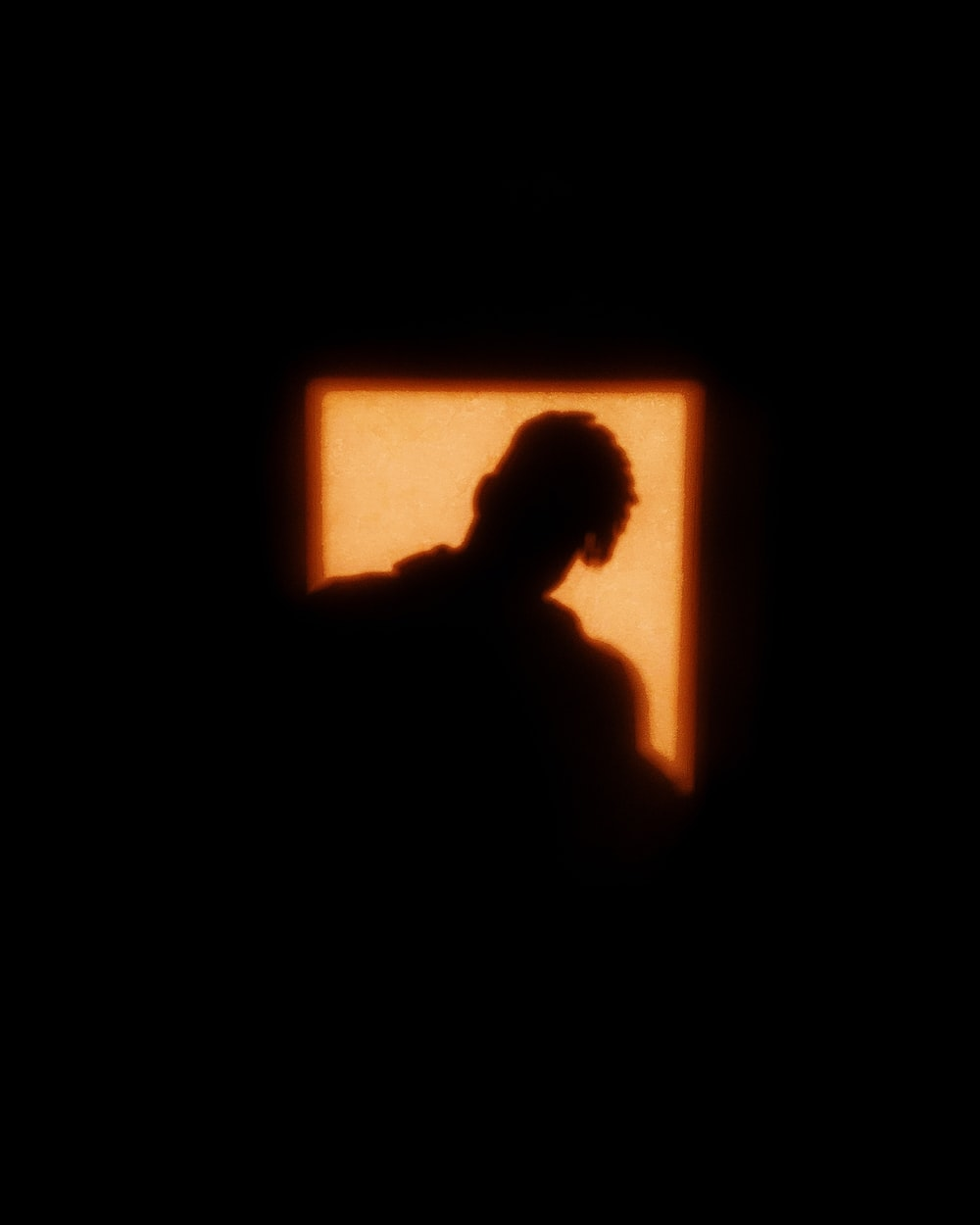 silhouette of man in front of window