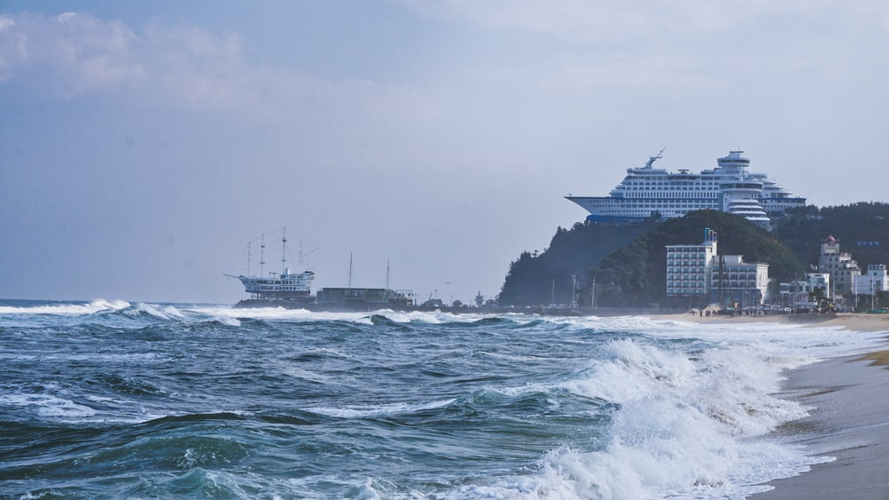 white ship on sea under white sky during daytime