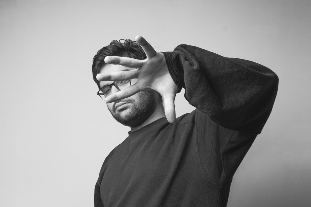 man in black crew neck shirt covering his face