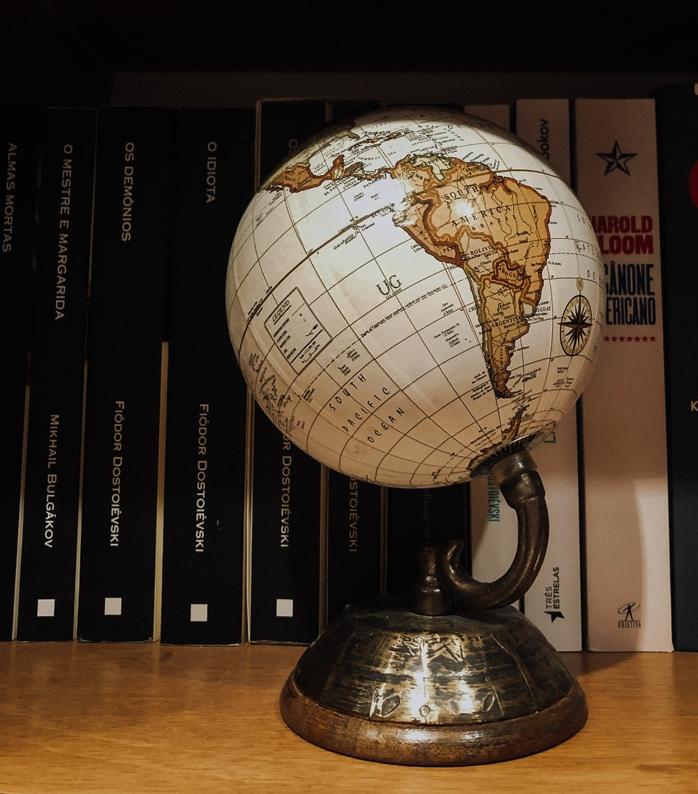 white and brown desk globe on brown wooden table